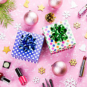 Make up cosmetics, presents and Christmas decorations on artistic pink background, copy space
