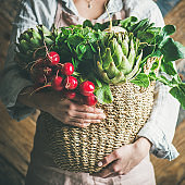 Female farmer holding basket with fresh vegetables, square crop