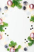Christmas background with fir tree branches, Christmas lights, pink and beige decorations, silver ornaments