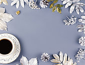 Winter concept flat lay with coffee drink and silver leaves, copy space. Christmas frame background.