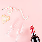 Valentine's day cookies, wine glasses and wine on pink background.