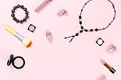 Woman fashion accessories, jewelry and cosmetics on pink background. Flat lay