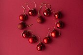 Red Christmas tree decorative toy balls on red celebratory Christmas background. New Year's holidays laid out in the shape of a heart. Christmas holidays.
