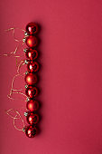 Red Christmas tree decorative toy balls on red celebratory Christmas background laid out in vertical line. New Year's holidays. Christmas holidays.