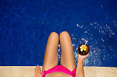 Girl holding coconut drink in the blue pool, slim legs, instagram style. Tropical fruit diet. Summer holiday