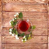 jasmine tea and jasmine flowers on  wooden background, top view