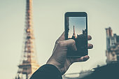 Young man making photograph of Eiffel Tower