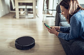 Lady using robot vacuum cleaner for help