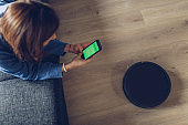 Girl using robot vacuum cleaner with mobile