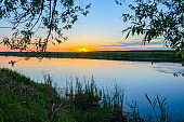Tranquil summer landscape with river and tree branches on a background of setting sun and sunset sky.