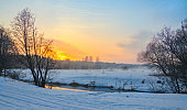 Frosty foggy winter landscape with small forest river and rising sun.