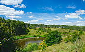 Sunny summer landscape with green hills,river curve and beautiful woods on a nice day