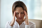 Woman feeling headache or migraine touching temples to relieve pain