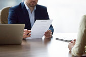 Serious HR executive interviewing woman student in office