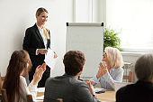 Executive team congratulating successful female manager with applause at meeting