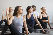 Group of young sporty people in Matsyendrasana pose, close up