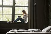 Smiling woman enjoying new bestseller book sitting on window sill