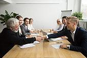 Senior investor buying startup handshaking young entrepreneur at group meeting