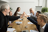 Diverse motivated young and senior business people giving high five