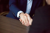 Close up of male partners handshaking after successful meeting