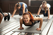 Woman doing difficult plank exercise or pushups at group training