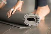 Girl unrolling grey fitness exercise mat for class, close up