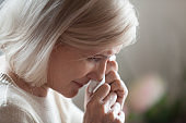 Close up of disappointed aged woman wiping tears crying