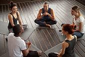 Diverse smiling people sitting on mats talking before yoga training