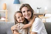 Happy loving young mother hugging little preschool daughter, portrait