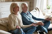 Senior couple meditating practicing yoga together sitting at home sofa