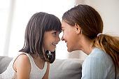 Mother and daughter touching with foreheads looking at each other
