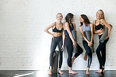 Group of young sporty girls with yoga mats, copyspace