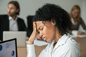 African businesswoman feeling unwell suffering from headache at team meeting