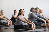 Group of young sporty people in paschimottanasana pose