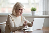 Happy mature businesswoman excited reading good news looking at laptop