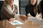 Diverse businesswomen shaking hands at group meeting or job interview
