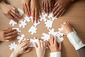 Hands of diverse people assembling jigsaw puzzle together, top view