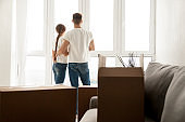 Couple looking through window planning future in new home
