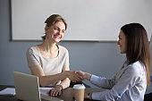 Smiling female partners shaking hands thanking for good teamwork result