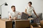 Smiling couple unpacking cardboard boxes with belongings