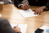 Businessman signing business contract at meeting, making partnership deal concept