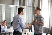 Ceo motivating rewarding male employee shaking hand congratulating with promotion