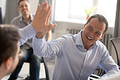 Happy friendly male colleagues giving high five celebrating business achievement
