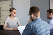 Confident female applicant smiling during job interview in office