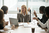 Stressed angry businesswoman arguing at meeting with male colleagues
