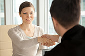 Smiling beautiful woman shaking male hand, arriving at job interview