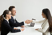 Smiling female applicant greeting HR managers with handshake
