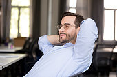 Confident businessman relaxing leaning back at workplace