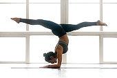 Young yogi attractive woman practicing yoga, doing Pincha Mayurasana
