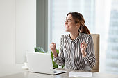 Excited businesswoman gesturing celebrating company online success